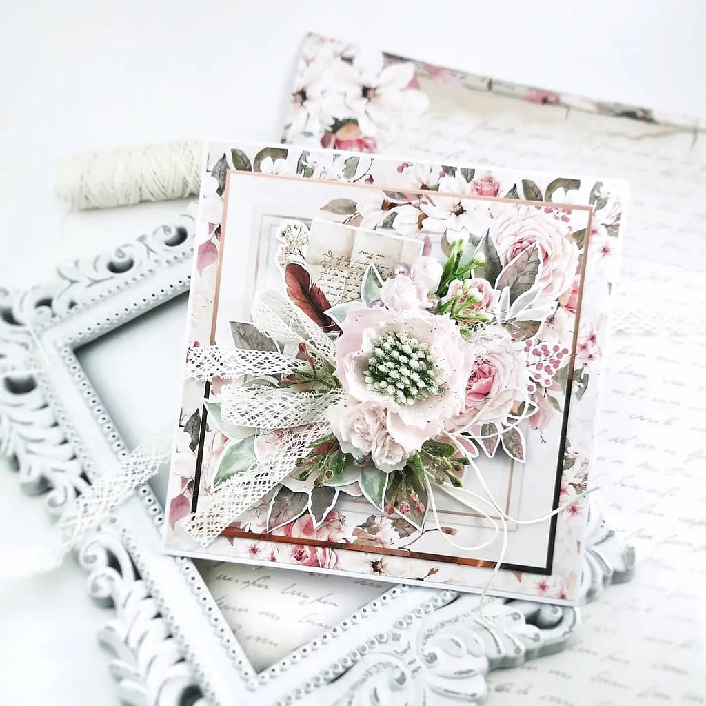 Bogato zdobiona kartka w kolorze różowym z ręcznie robionymi kwiatami. Rękodzieło w prezencie urodzinowym, imieninowym. Pomysł na kartkęślubną.