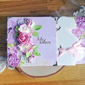 Różowy album ciążowy ozdobiony techniką scrapbooking. Strony oklejone różowymi oraz kremowymi papierami w kwiaty. Idealny prezent dla przyszłej mamy spodziewającej się dziewczynki.