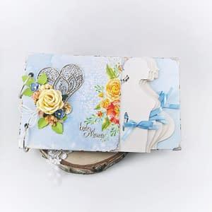 Błękitny album ciążowy z serduszkiem. Album ciążowy ozdobiony techniką scrapbooking. Strony oklejone papierami w odcieniach niebieskiego i szarego. Idealny prezent dla przyszłej mamy spodziewającej się chłopca.