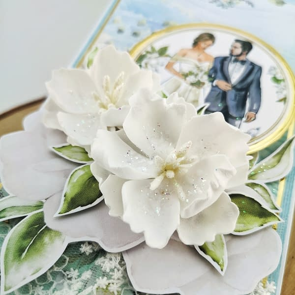 Błękitna kartka ślubna ze złotymi elementami. Do kartki mogę dodać kieszonkęna pieniądze oraz personalizowane życzenia.